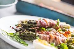 Φρέσκο σπαράγγι που τυλίγεται στο μπέϊκον σε ένα άσπρο πιάτο με το arugula Στοκ φωτογραφίες με δικαίωμα ελεύθερης χρήσης