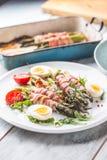 Φρέσκο σπαράγγι που τυλίγεται στο μπέϊκον σε ένα άσπρο πιάτο με το arugula Στοκ Φωτογραφία