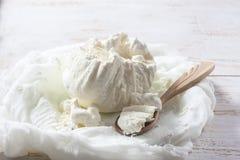 Φρέσκο σπιτικό τυρί εξοχικών σπιτιών cheesecloth στο άσπρο ξύλινο TA Στοκ Εικόνες