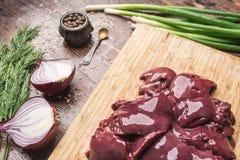 Φρέσκο συκώτι κοτόπουλου σε κόκκινων και πράσινων κρεμμύδια πινάκων κοπής, άνηθος σε ένα ξύλινο υπόβαθρο Στοκ Εικόνες