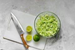 Φρέσκο τεμαχισμένο λάχανο για τη σαλάτα και τις φέτες του φρέσκου ασβέστη στοκ φωτογραφίες