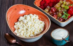 Φρέσκο τυρί εξοχικών σπιτιών με τα juicy σμέουρα, τη φράουλα και τα σταφύλια μούρων στο σκοτεινό ξύλινο υπόβαθρο στοκ φωτογραφία με δικαίωμα ελεύθερης χρήσης