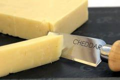 Φρέσκο τυρί τυριού Cheddar περικοπών σε έναν πίνακα πλακών στοκ φωτογραφία