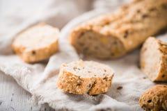 Φρέσκο, υγιές ολόκληρο baguette σίκαλης σιταριού με τις φέτες στο ύφασμα Στοκ εικόνες με δικαίωμα ελεύθερης χρήσης