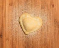 Φρέσκο, χειροποίητο, ενιαίο raviolo με μορφή της καρδιάς, που καλύπτεται με το αλεύρι και που τοποθετείται στον ξύλινο πίνακα και Στοκ φωτογραφία με δικαίωμα ελεύθερης χρήσης
