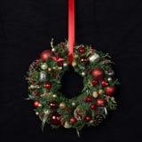 Φρέσκο χειροποίητο στεφάνι Χριστουγέννων που διακοσμείται με τις κόκκινους και χρυσούς διακοσμήσεις Χριστουγέννων, τους έλατο-κών Στοκ Εικόνες