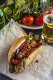 Φρέσκο χοτ ντογκ με την ντομάτα, το κρεμμύδι και το μαρούλι και το γυαλί μπύρας Στοκ φωτογραφία με δικαίωμα ελεύθερης χρήσης