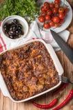 Φρέσκο ψημένο Lasagne στο κόκκινο πιάτο με τις μαύρες ντομάτες ελιών και τσίλι στον ξύλινο πίνακα Στοκ Φωτογραφίες