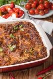 Φρέσκο ψημένο Lasagne στο κόκκινο πιάτο με τις μαύρες ντομάτες ελιών και τσίλι στον ξύλινο πίνακα Στοκ φωτογραφία με δικαίωμα ελεύθερης χρήσης
