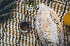 Φρέσκο ψωμί και ψημένα αγαθά στον ξύλινο τεμαχίζοντας πίνακα Στοκ Φωτογραφία