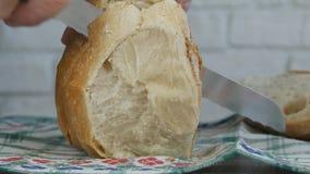 Φρέσκο ψωμί που τεμαχίζεται με ένα μαχαίρι στον πίνακα στοκ εικόνα