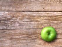 Φρέσκο ώριμο πράσινο μήλο στο φυσικό ξύλινο υπόβαθρο Ταπετσαρία φθινοπώρου στοκ εικόνα με δικαίωμα ελεύθερης χρήσης