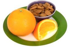 Φρέσκο ώριμο Juicy πορτοκάλι με το υγιές πρόχειρο φαγητό καρυδιών αμυγδάλων Στοκ εικόνες με δικαίωμα ελεύθερης χρήσης
