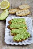 Φρέσκο crostini με το αβοκάντο guacamole στην άσπρη κινηματογράφηση σε πρώτο πλάνο πιάτων στον αγροτικό ξύλινο πίνακα στοκ εικόνες