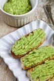 Φρέσκο crostini με το αβοκάντο guacamole στην άσπρη κινηματογράφηση σε πρώτο πλάνο πιάτων στον αγροτικό ξύλινο πίνακα στοκ φωτογραφία