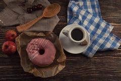 Φρέσκο doughnut με τον καφέ στον ξύλινο πίνακα με την πετσέτα, το κουτάλι και το γ Στοκ εικόνα με δικαίωμα ελεύθερης χρήσης