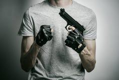 Φρίκη και θέμα πυροβόλων: ο δολοφόνος με ένα πυροβόλο όπλο σε δικοί του παραδίδει τα μαύρα γάντια σε ένα γκρίζο υπόβαθρο στο στού Στοκ Φωτογραφία