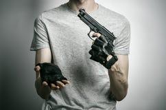 Φρίκη και θέμα πυροβόλων: ο δολοφόνος με ένα πυροβόλο όπλο σε δικοί του παραδίδει τα μαύρα γάντια σε ένα γκρίζο υπόβαθρο στο στού Στοκ Εικόνες