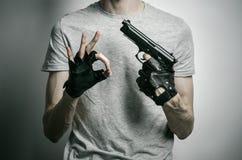 Φρίκη και θέμα πυροβόλων: ο δολοφόνος με ένα πυροβόλο όπλο σε δικοί του παραδίδει τα μαύρα γάντια σε ένα γκρίζο υπόβαθρο στο στού Στοκ εικόνες με δικαίωμα ελεύθερης χρήσης
