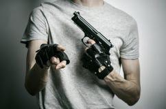 Φρίκη και θέμα πυροβόλων: ο δολοφόνος με ένα πυροβόλο όπλο σε δικοί του παραδίδει τα μαύρα γάντια σε ένα γκρίζο υπόβαθρο στο στού Στοκ εικόνα με δικαίωμα ελεύθερης χρήσης