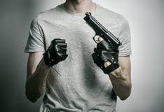 Φρίκη και θέμα πυροβόλων: ο δολοφόνος με ένα πυροβόλο όπλο σε δικοί του παραδίδει τα μαύρα γάντια σε ένα γκρίζο υπόβαθρο στο στού Στοκ Εικόνα