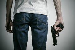 Φρίκη και θέμα πυροβόλων: τρελλός δολοφόνος με ένα πυροβόλο όπλο σε ένα γκρίζο υπόβαθρο στο στούντιο Στοκ Εικόνες
