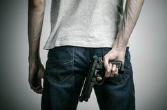 Φρίκη και θέμα πυροβόλων: τρελλός δολοφόνος με ένα πυροβόλο όπλο σε ένα γκρίζο υπόβαθρο στο στούντιο Στοκ φωτογραφία με δικαίωμα ελεύθερης χρήσης