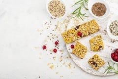 Φραγμοί δημητριακών με τα κόκκινα μούρα, μέλι για ένα υγιές πρόχειρο φαγητό σε ένα ελαφρύ υπόβαθρο με τους σπόρους λιναριού, σουσ Στοκ φωτογραφία με δικαίωμα ελεύθερης χρήσης