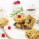 Φραγμοί δημητριακών με τα κόκκινα μούρα, μέλι για ένα υγιές πρόχειρο φαγητό σε ένα ελαφρύ υπόβαθρο με τους σπόρους λιναριού, σουσ Στοκ Φωτογραφία