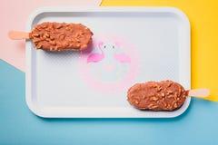 Φραγμοί παγωτού σοκολάτας επιδορπίων με τα καρύδια, ξύλινο ραβδί στο μπλε και κίτρινο υπόβαθρο κρητιδογραφιών Εσκιμώος στον μπλε  Στοκ Εικόνες