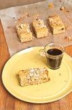 Φραγμοί πεκάν βερίκοκων στο κίτρινο πιάτο με το γυαλί του espresso και περισσότεροι φραγμοί που δροσίζουν σε χαρτί περγαμηνής Στοκ Φωτογραφίες