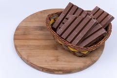 Φραγμοί σοκολάτας στο υφαμένο καλάθι πέρα από το λευκό Στοκ Εικόνες