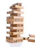 Φραγμοί του jenga παιχνιδιών στο άσπρο υπόβαθρο Κάθετο σύνολο πύργων και στο παιχνίδι Ξύλινοι φραγμοί στο σωρό με το ψηφίο αριθμώ Στοκ Εικόνες