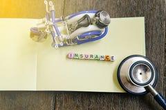 Φραγμός ΑΣΦΑΛΙΣΤΙΚΗΣ λέξης στο σημειωματάριο με την ελαφριά επίδραση το αναμνηστικό και stetoscope στο ξύλινο υπόβαθρο Στοκ φωτογραφίες με δικαίωμα ελεύθερης χρήσης
