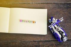 Φραγμός ΑΣΦΑΛΙΣΤΙΚΗΣ λέξης στο σημειωματάριο με την ελαφριά επίδραση το αναμνηστικό και το ξύλινο υπόβαθρο Στοκ Εικόνες