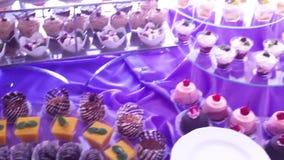 Φραγμός γαμήλιων καραμελών Εύγευστος γλυκός μπουφές με τα cupcakes απόθεμα βίντεο