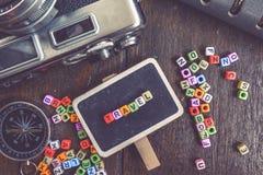 Φραγμός λέξης ΤΑΞΙΔΙΟΥ στο ξύλινο σύστημα σηματοδότησης, την πυξίδα και την εκλεκτής ποιότητας κάμερα εξασθενισμένο χρώμα επίδρασ Στοκ Φωτογραφία