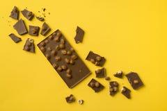 Φραγμός σοκολάτας με τα διεσπαρμένα κομμάτια Στοκ Φωτογραφίες