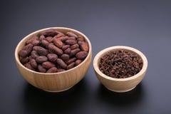 Φραγμός σοκολάτας και ξηρός λοβός κακάου, nibs κακάου στο ξύλινο κύπελλο επάνω Στοκ Εικόνες