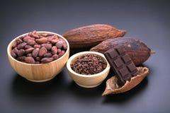 Φραγμός σοκολάτας και ξηρός λοβός κακάου, nibs κακάου στο ξύλινο κύπελλο επάνω Στοκ εικόνα με δικαίωμα ελεύθερης χρήσης