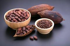 Φραγμός σοκολάτας και ξηρός λοβός κακάου, nibs κακάου στο ξύλινο κύπελλο επάνω Στοκ εικόνες με δικαίωμα ελεύθερης χρήσης