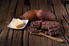 Φραγμός σοκολάτας, ξηροί λοβός κακάου και βούτυρο κακάου στο ξύλινο backgr Στοκ φωτογραφία με δικαίωμα ελεύθερης χρήσης