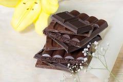 Φραγμός σοκολάτας που συσσωρεύεται σε ελαφρύ χαρτί που περιβάλλεται από τα λουλούδια Ένας πύργος των κύβων σοκολάτας Στοκ φωτογραφία με δικαίωμα ελεύθερης χρήσης
