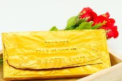 Φραγμός σοκολάτας που τυλίγεται στη χρυσή Ford Συμπίεση επιστολών τύπων Στοκ φωτογραφία με δικαίωμα ελεύθερης χρήσης