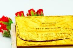 Φραγμός σοκολάτας που τυλίγεται στη χρυσή Ford Συμπίεση επιστολών τύπων Στοκ Φωτογραφία