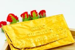 Φραγμός σοκολάτας που τυλίγεται στη χρυσή Ford Συμπίεση επιστολών τύπων Στοκ Εικόνες