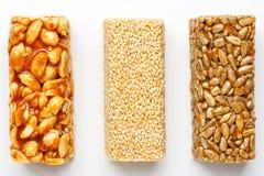 Φραγμός granola σιταριού με τα φυστίκια, το σουσάμι και τους σπόρους σε μια σειρά σε ένα άσπρο υπόβαθρο Η τοπ άποψη τρία ανάμεικτ στοκ φωτογραφία