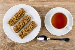 Φραγμός Granola στο πιάτο, φλυτζάνι του τσαγιού στο πιατάκι, κουταλάκι του γλυκού Στοκ εικόνες με δικαίωμα ελεύθερης χρήσης