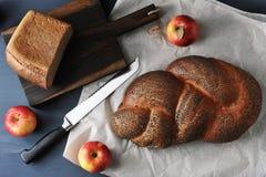 Φραντζόλα με τους σπόρους παπαρουνών και τη μισή από τη ληφθείσα ψωμί κινηματογράφηση σε πρώτο πλάνο - appl Στοκ Εικόνες