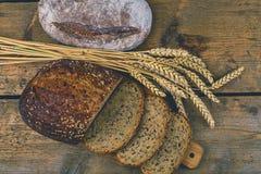 Φραντζόλες του ψωμιού, φέτες του ψωμιού και αυτιά του σιταριού στο ξύλινο υπόβαθρο Αγροτική και αγροτική έννοια κλείστε επάνω Στοκ Φωτογραφίες